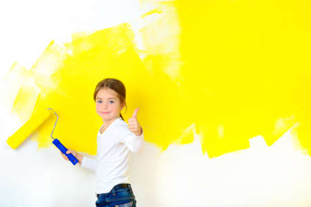 beautiful girl paints a roller with a wall in the room, smiling and shows class