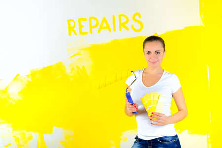 girl holds a cushion and chooses a color for painting the walls, on the wall inscription repairs