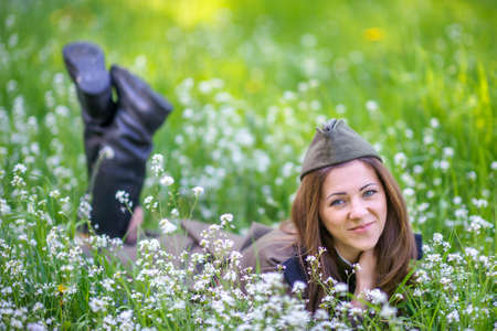 Girl in military uniform lies on fresh spring grass and smiling