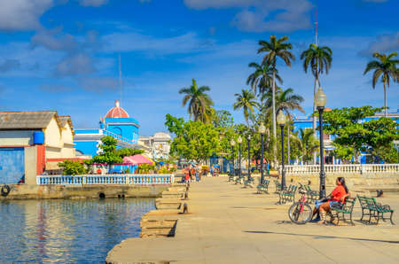 people rest on the waterfront in a provincial town, Cuba