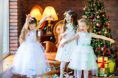 three cheerful girls in beautiful dresses are having fun near the festive Christmas tree, throwing candy and laughing 版權商用圖片