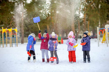 cheerful friends play in a winter park, throw snow and have fun 版權商用圖片