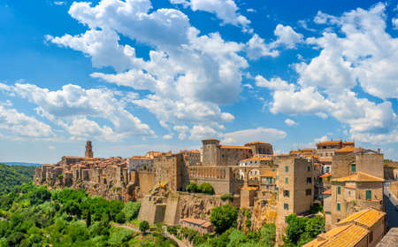 Panorama of the medieval town of Pitigliano located on the edge of the cliff, with beautiful clouds in the sky, Tuscany. Italy. Europe