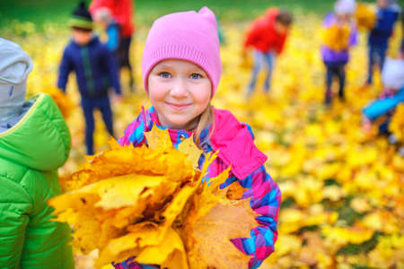 smiling girl with a bouquet of intense autumn leaves