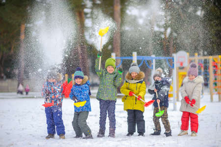 cheerful children play in a winter park, throw snow and have fun