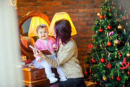 mother reads fairy tales to her daughter while sitting near a festive Christmas tree 版權商用圖片