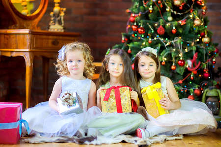 Three girls in dresses with gifts in their hands are sitting on the floor near the festive Christmas tree. 版權商用圖片