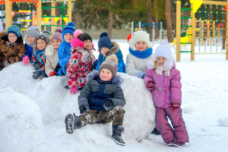A large group of friends are resting on large snowballs, on a winter playground