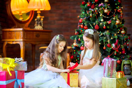 beautiful girls in dresses sit on the floor near the festive Christmas tree and open presents, Christmas morning