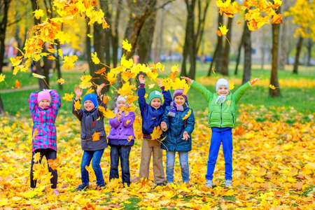 A large group of friends playing and having fun in a beautiful autumn park, throwing leaves and laughing