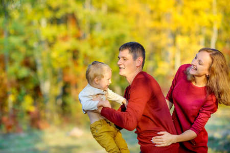 happy family playing and having fun in a beautiful autumn park