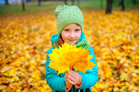 beautiful girl holding autumn leaves in hands