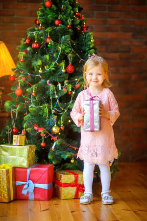 happy little girl with a gift in hands near the Christmas tree Stockfoto