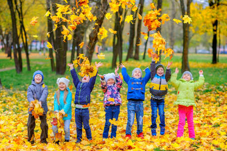 happy cheerful children play toss foliage in a beautiful autumn park