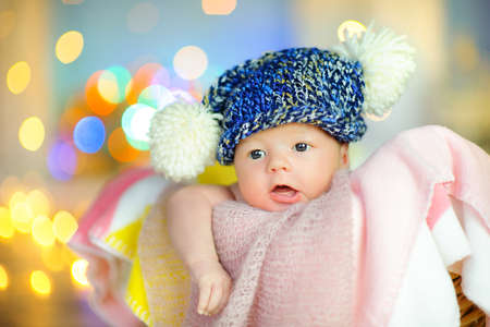 newborn baby in a hat in a basket on the background of bright lights