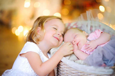 girl holds her hand and gently snuggles up to her little sister, amid bright lights 写真素材