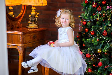 beautiful little girl in a dress sits in an armchair with a gift in hand, near the holiday tree