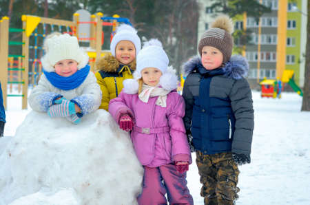 children play with snow on the playground