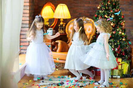 Kids having fun and celebrating near the Christmas tree.