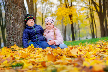 little guy with a girl sitting near a tree on the autumn foliage