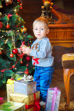 funny baby decorates the Christmas tree with balls, a lot of gifts under the Christmas tree