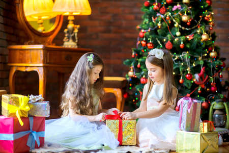 girls in beautiful dresses are sitting on the floor near the Christmas tree, open gifts 版權商用圖片