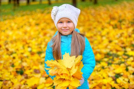 teen girl with beautiful bouquet of autumn foliage in autumn park