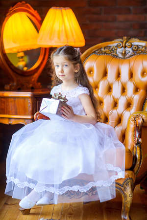 beautiful little girl in a white dress holds a gift while sitting in a chair, Christmas morning 版權商用圖片