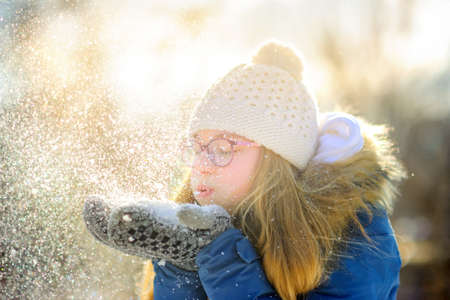 happy teen girl in beautiful park at sunset, inflates snow crystals