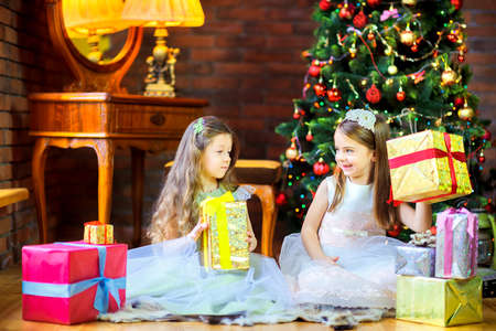 girls in beautiful dresses sitting on the floor near the Christmas tree give each other gifts