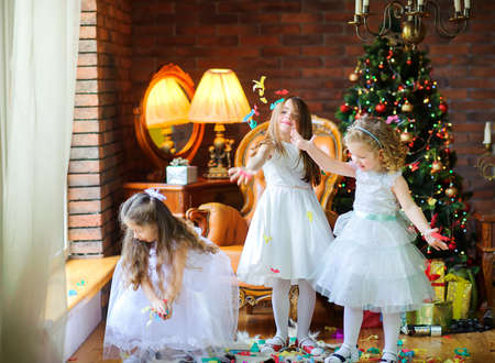 three little girls in dresses playing colorful candy in the room near the festive Christmas tree 版權商用圖片