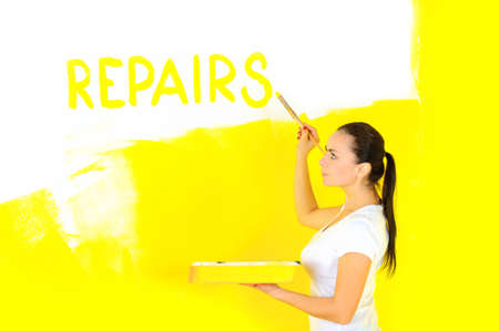 woman painter holding a bathtub with paint and writing a brush on the wall of the word repair
