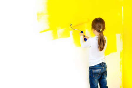 a little girl paints painfully the walls with a roller in the room