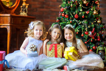 three beautiful girls are sitting on the floor with gifts in hands, in the background a festive Christmas tree 版權商用圖片