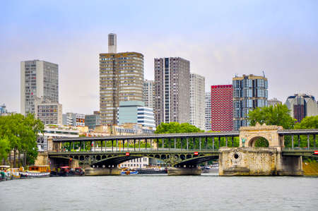 modern neighborhoods of Paris, high-rise buildings on the embankment of the river Seine in the evening Фото со стока