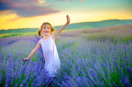 beautiful little girl is walking and having fun on the lavender field at sunset