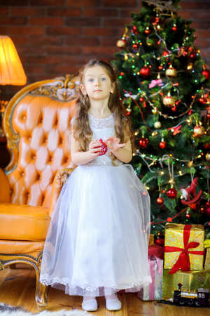 little girl in a dress decorates with balls festive Christmas tree