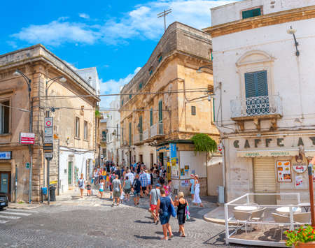 Italy, Ostuni, July 2018 - panorama of a tourist street in the historical part of the city