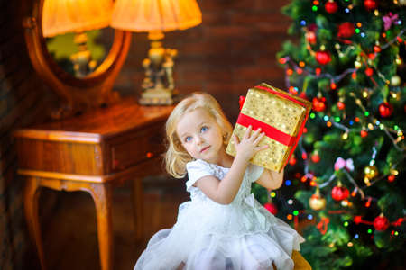 beautiful little girl in a festive dress opens a gift sitting near a Christmas tree