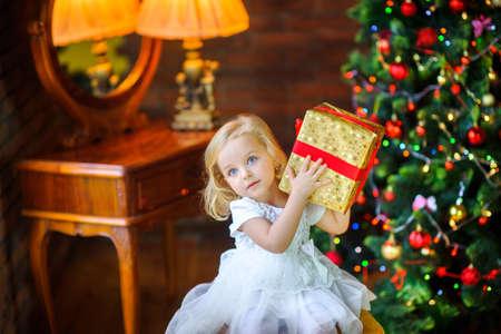 la bella bambina in un vestito festivo apre un regalo seduto vicino a un albero di Natale