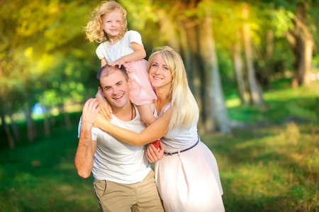 Happy family in a beautiful spring park, daughter around dad's neck, healthy outdoor recreation