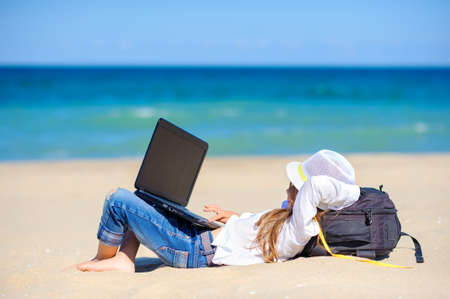 work in travel, girl teenager in a beach hat lies on the beach with a laptop