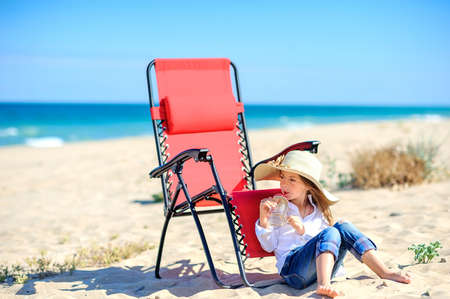 Beautiful little girl in a beach hat sits on the beach near the chair and drinks fresh juice, healthy rest by the sea