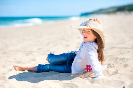 Beautiful little girl in a beach hat is sitting on the beach playing and smiling, healthy rest by the sea