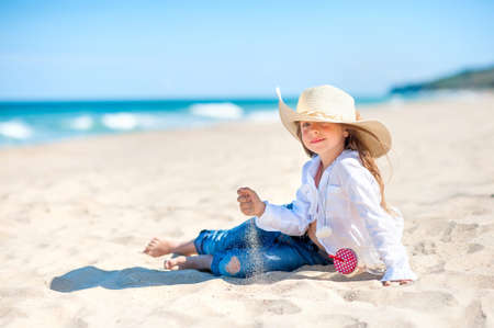 Beautiful little girl in a beach hat sits on the beach and plays with sand, healthy rest by the sea