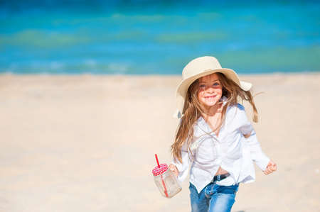 Beautiful little girl in a beach hat playing and having fun by the sea, with a mug of juice in her hand