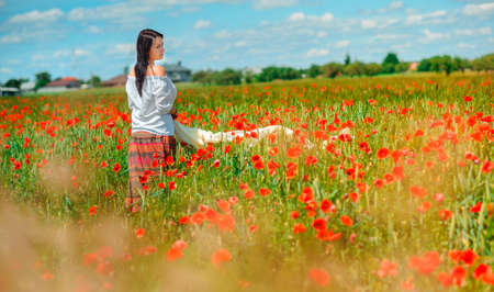 Beautiful girl walks in a poppy field, holding petals in her hands, spring mood