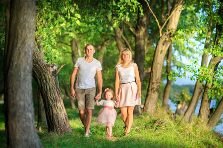 Happy family walks in a beautiful spring park, holding hands and smiling, healthy outdoor recreation 版權商用圖片