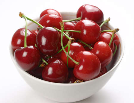 Closeup of cup of cherries on white background