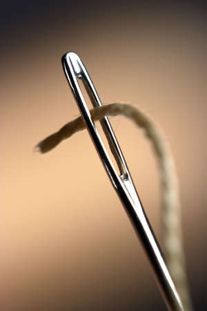Needle with thread on dark background;